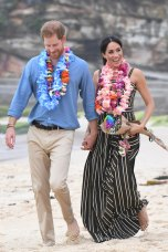 Britain's Prince Harry, the Duke of Sussex and his wife Meghan, the Duchess of Sussex catch the beach vibe.