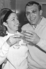 His face battered and blackened, Bobby Skilton joins his wife Marion in a champagne toast at their home after the Brownlow win.