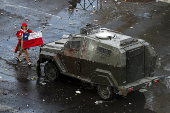 A demonstrator holds a Chilean flag toward an armored police vehicle Chile's capital, Santiago, this week.