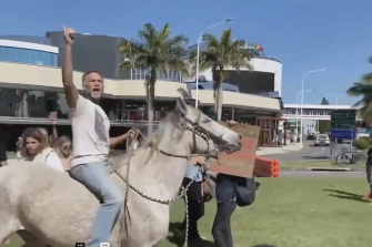 Protesters, including a horseback-riding Michael Corrigan, along the NSW-Queensland border in Coolangatta last Sunday.