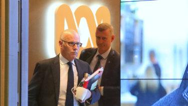 The ABC's executive editor John Lyons is followed by an AFP officer during Wednesday's raids.