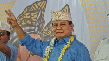 Prabowo Subianto pictured at an event in Bali waving a 'V' for victory sign,  or maybe '2', his ballot number, to his volunteers.