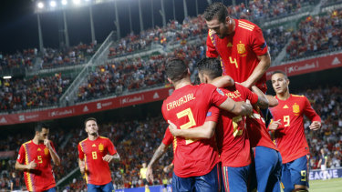 Sergio Ramos celebrates with teammates after scoring Spain's fifth goal.