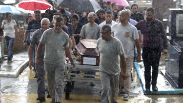 Cemetery employees carry the coffin of Kaio Limeira, 15.