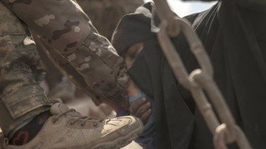 A woman kisses the hand of a soldier after leaving the IS stronghold.