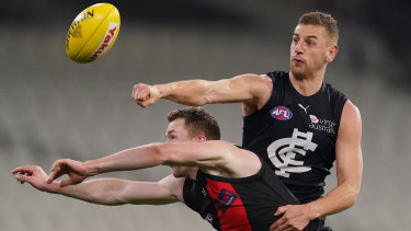 Pulling no punches: Carlton's Liam Jones clears ahead of Essendon's Jacob Townsend.