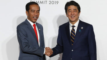 Getting on with it: Indonesian President Joko Widodo, left, is welcomed by Japanese Prime Minister Shinzo Abe in Osaka, a few hours after the court's decision confirming his election win.