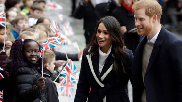 Prince Harry and his fiance Meghan Markle are greeted by flag-waving school children in Birmingham.