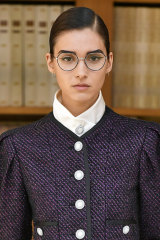 Model Rachelle Harris wearing winged eyeliner and lashes under glasses at the Chanel Paris Haute Couture Week show in July.