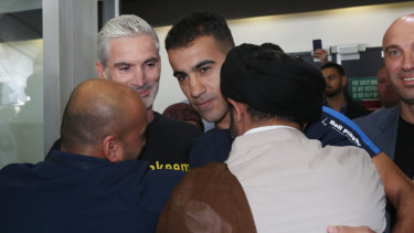 Former Socceroo Craig Foster (left) is seen with refugee footballer Hakeem Al-Araibi (centre) as he is greeted by supporters upon arriving at Melbourne International Airport in Melbourne, Tuesday, February 12, 2019.