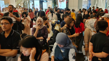 People stand outside a shopping mall following an earthquake in Jakarta.