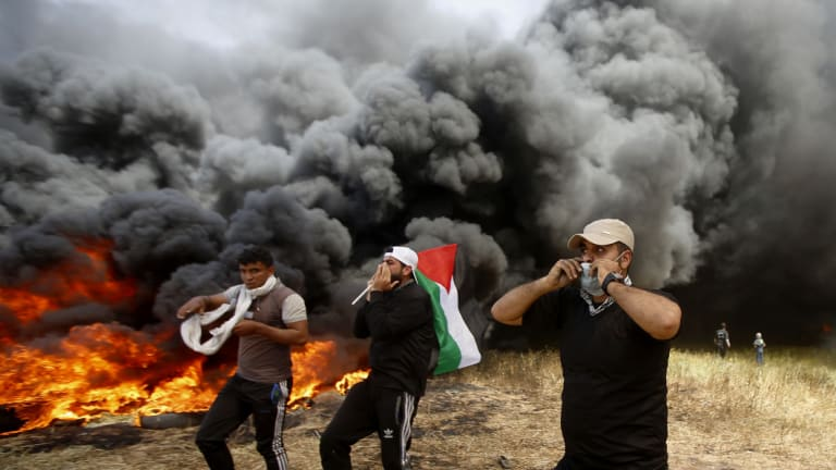 Palestinian protesters chant slogans next to burning tires during clashes with Israeli troops along Gaza's border with Israel, east of Khan Younis, Gaza Strip.