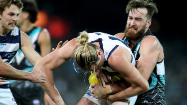 Port Adelaide's Charlie Dixon tackles Geelong's Mark Blicavs at Adelaide Oval.