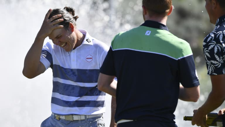 Winner: Jake McLeod is sprayed with champagne on the 18th green.