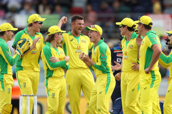 The Australian team celebrate the wicket of Virat Kohli in Canberra on Wednesday. A far bigger contest is playing out behind the scenes.