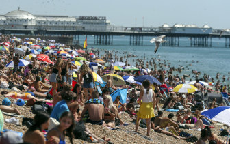 People crowd onto the beach at Brighton, England.