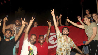 Demonstrators celebrate with a Tunisian national flag during a rally after the president suspended the legislature and fired the prime minister in Tunis, Tunisia.