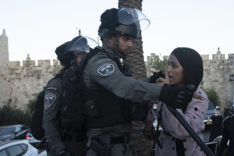 An Israeli border police officer faces off with a Palestinian woman at a protest at the Damascus Gate to the Old City of Jerusalem Thursday, June 17, 2021.