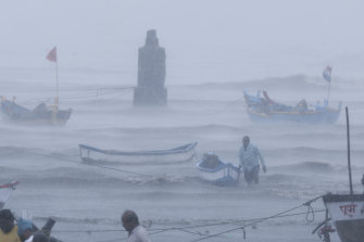 A fisherman waits for help as he tries to move a fishing boat to safer ground on the Arabian Sea coast in Mumbai on Monday.