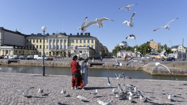 Tourists feed seagulls in front of the Presidential palace in Helsinki, Finland. The city will play host to a Trump-Putin meeting in July.