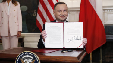 Polish President Andrzej Duda holds up an agreement signed with Donald Trump in the Diplomatic Reception Room of the White House.