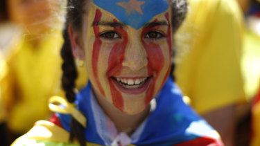 A protester with her face covered in the Catalan independence flag.