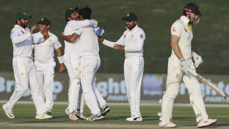 Bowled over: Pakistan celebrate taking the first wicket of Australia's second innings, after Shaun Marsh (right) was dismissed by Sarfaraz Ahmed (third left).