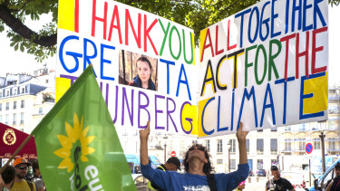 """A climate activist holds a placard reading """"Thank You Greta Thunberg """" next to the French National Assembly during Greta Thunberg's visit to Paris last week."""