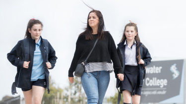 Casey Knight walks with children Stella and Matilda, who face another school move due to lack of funding.