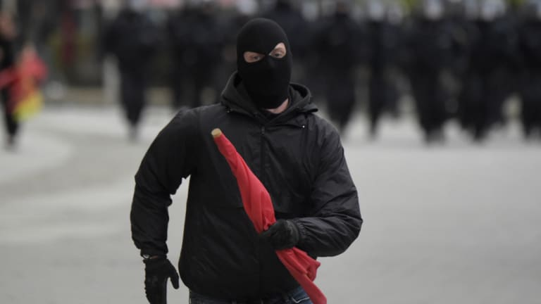 A masked leftist demonstrator flees approaching police who try to separate leftist and nationalist demonstrators in Chemnitz, eastern Germany, on Saturday.