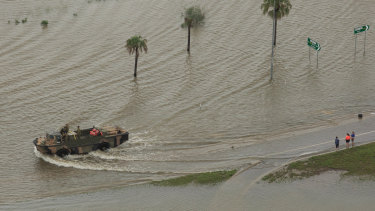 An army vehicle pushes through floodwater in Townsville.