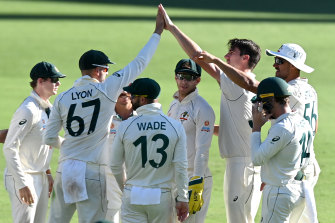 The Aussies celebrate Cummins' fourth wicket.