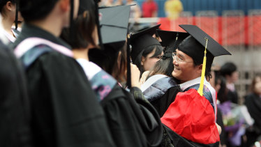 Chinese students attend a graduation ceremony at Fudan University in Shanghai. The university is one of three that have revised their charters to reflect Communist Party doctrine.