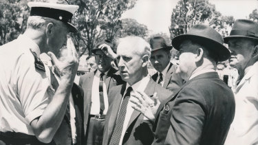 Senior police talk with Mr. Vernon Wilcox, Victorian Minister for Transport (centre) and Mr. E. H. Brownbill, Chairman of the Victorian Railway Commission (right) at the accident.