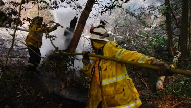 Kurrajong Heights firefighters work on  burnt-out bushland at Berambing on Monday ahead of ominous forecasts this week.