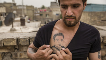 Munther al-Sudani, the brother of Captain Harith al-Sudani, shows off a tattoo of his late brother in Baghdad.