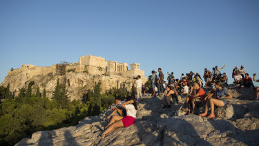 Tourists sit under the Parthenon and watch the sunset over Athens.