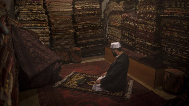 Noorullah Ahmadi prays at his shop, Handy Crafts Jewelers Store, on Chicken Street in Kabul.