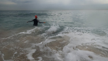 A swimmer at Coogee as storm clouds hover.
