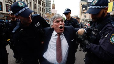 A man is taken away by police during the protest in Sydney.
