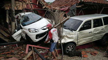 A man clears debris in front of damaged cars and buildings at the Villa Avi Redita in Carita.
