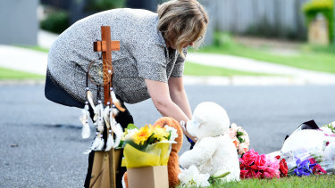 Mourners pay their respects at the scene where Ms Clarke and her children were killed in a deliberately lit car fire in Camp Hill.