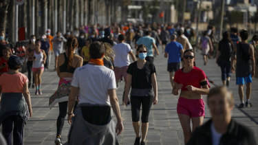 People exercise on a seafront promenade in Barcelona