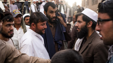 Zindani, centre, and his friend Kitab, in white, at a mosque during a discussion with marchers and other worshippers.