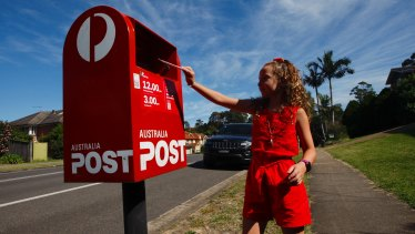 Eight-year-old Scarlett Frost drops a letter off at the local postbox. Writing letters has become one of her favourite pastimes.