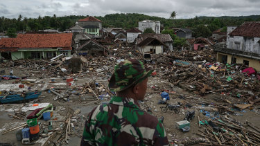 An Indonesian soldier looks at damaged houses and debris in Sumur.