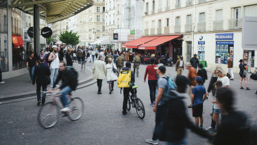 A Glovo food delivery courier waits for an order at Les Halles in Paris.