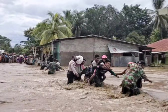 Soldiers and police officers assist residents to cross a flooded road in Malaka Tengah, East Nusa Tenggara province, Indonesia, on Monday, April 5, 2021.