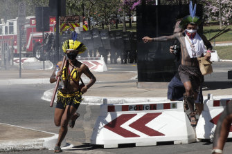 Indigenous protesters run from police outside Congress in Brasilia, Brazil, after being barred from entering.