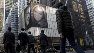 Pedestrians walk by photographs of Harry Macklowe and his new wife, Patricia Landeau, at 432 Park Ave., in New York.